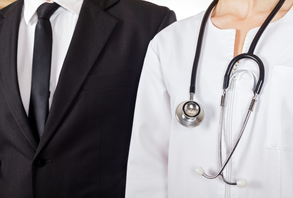 Closeup of a businessman and a female physician standing shoulder to shoulder
