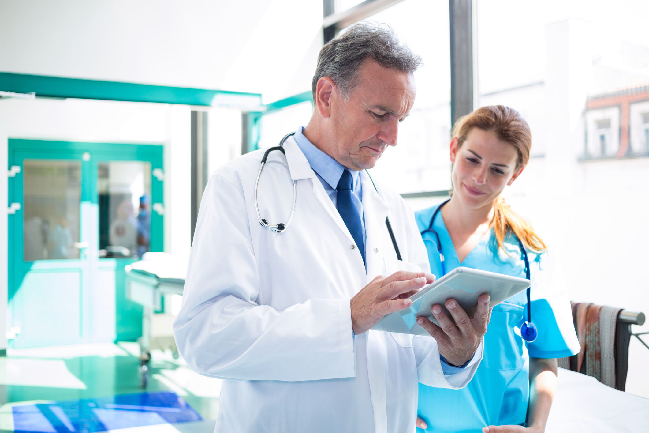 Two physicians in a hospital setting look at a tablet together