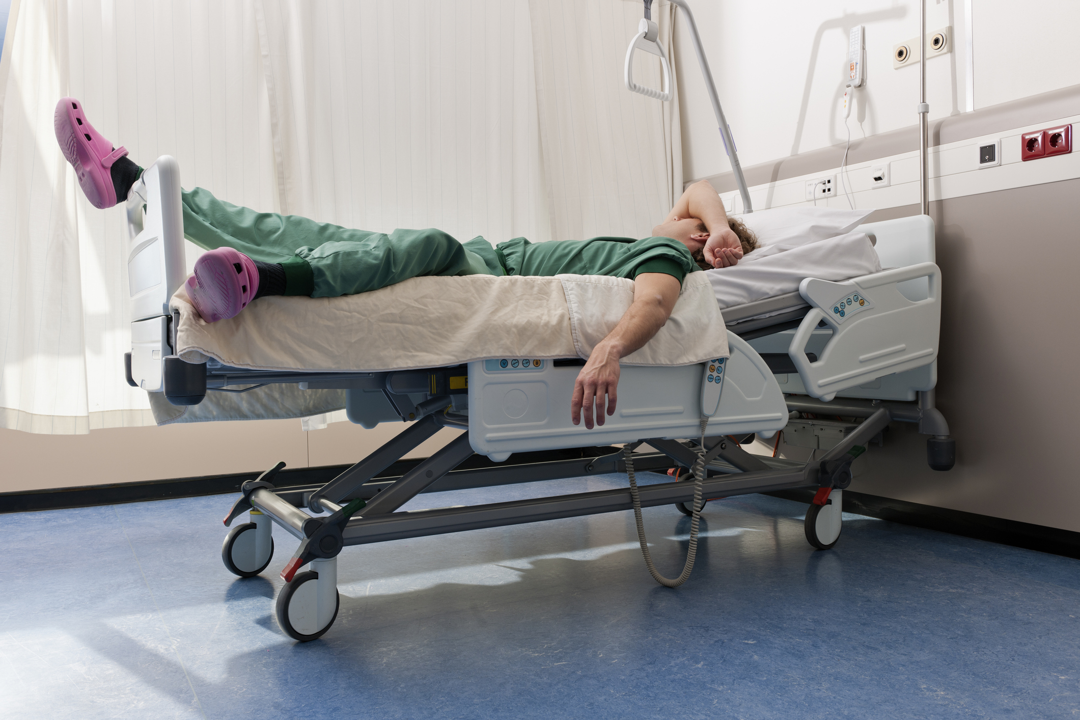 Exhausted healthcare worker lying on hospital bed for nap