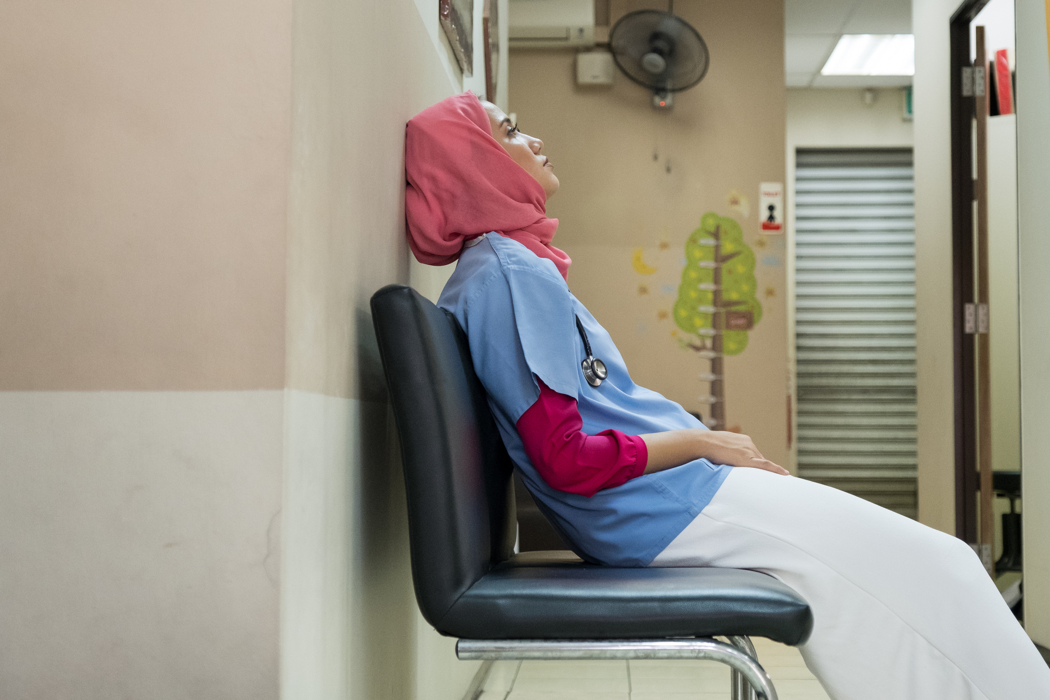 Young female physician wearing a hijab and looking exhausted in a clinic