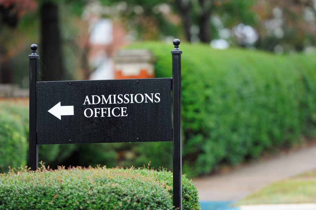Outdoor view of sign pointing to direction of admissions office