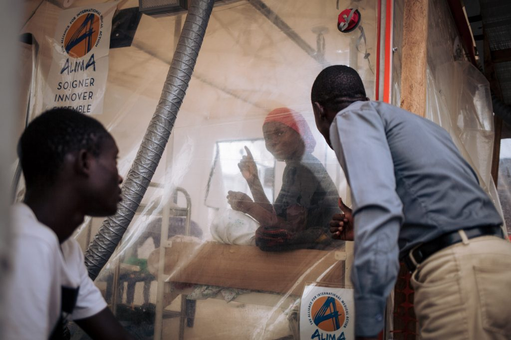 A woman speaks to health workers through the transparent wall of an isolation tent in an Ebola treatment centre