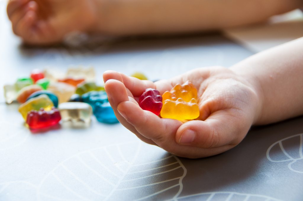 Close-up of multi-colored gummies in a child's hand