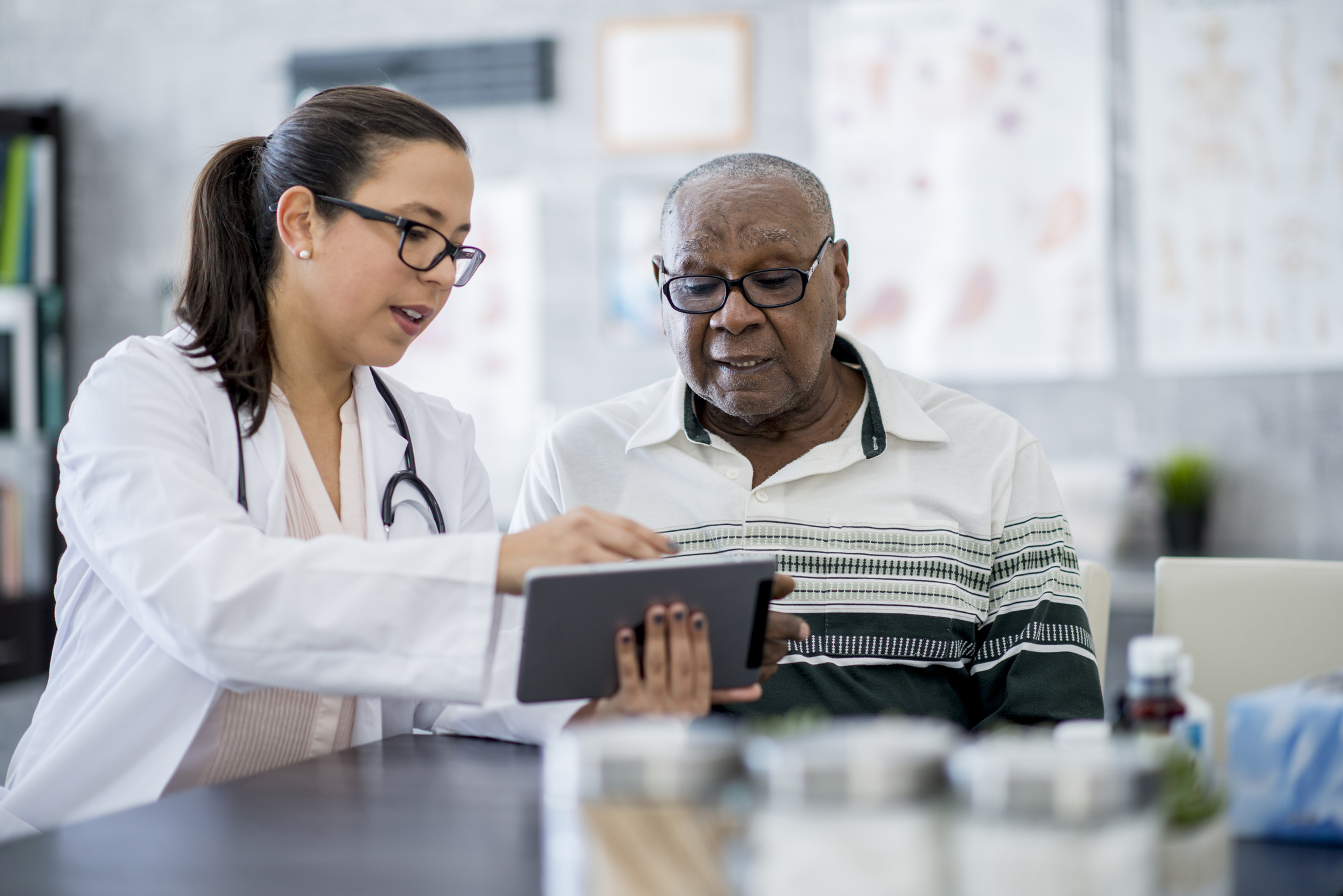 Young white physician showing a tablet to an elderly Black patient