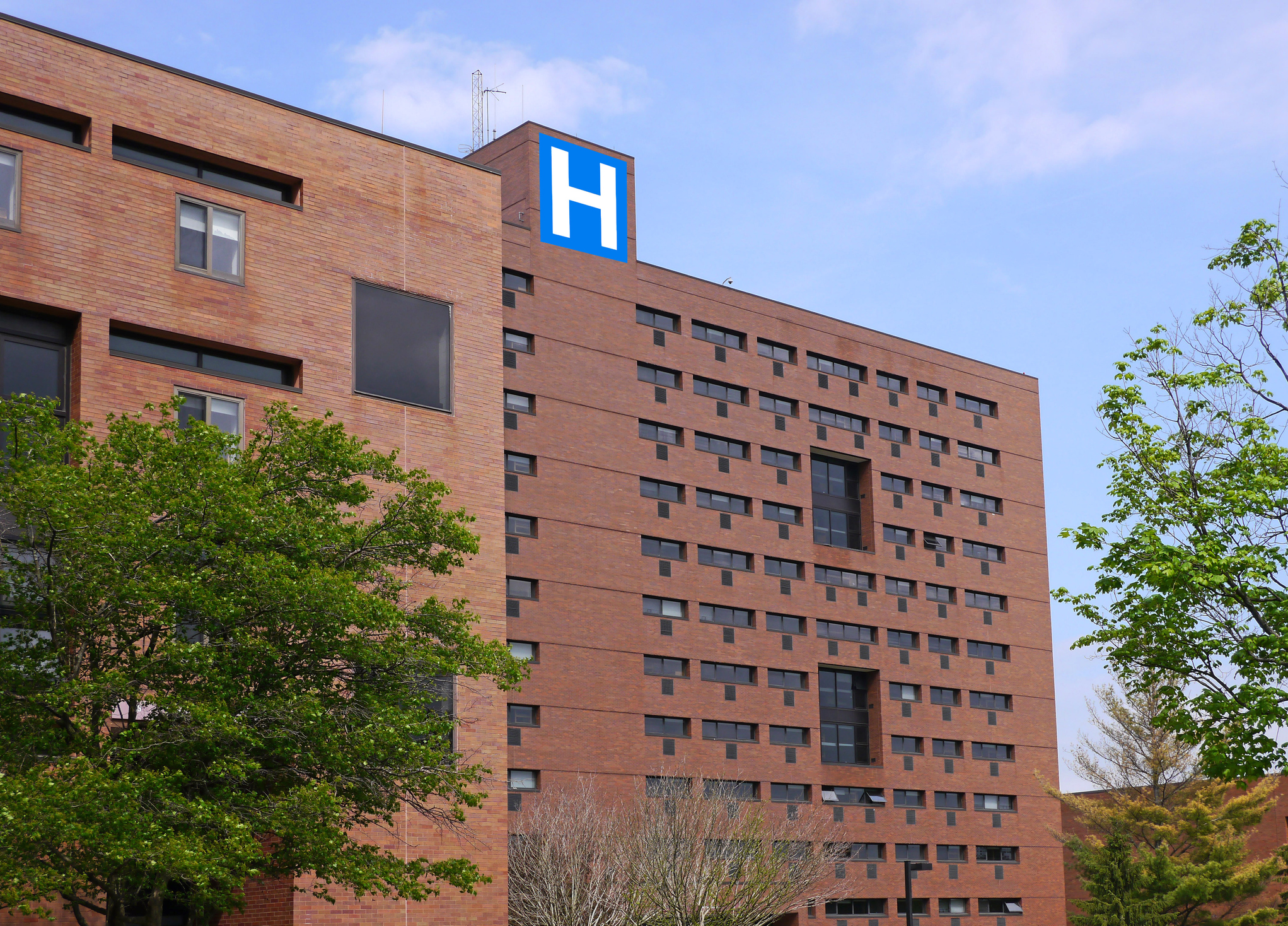 Exterior of a large brick hospital with 'H' sign