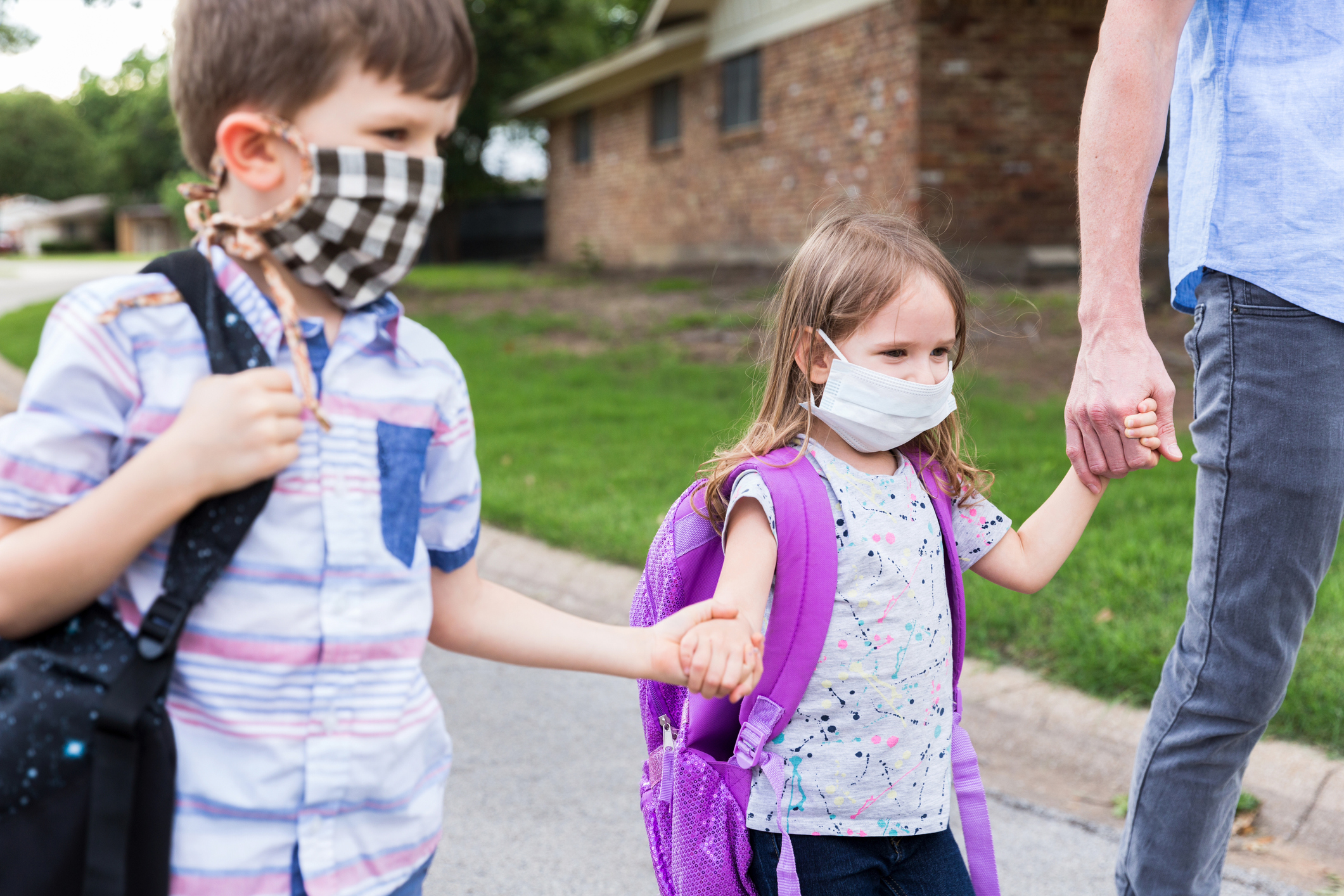 Two children wearing face masks hold hands walking home with their dad after school