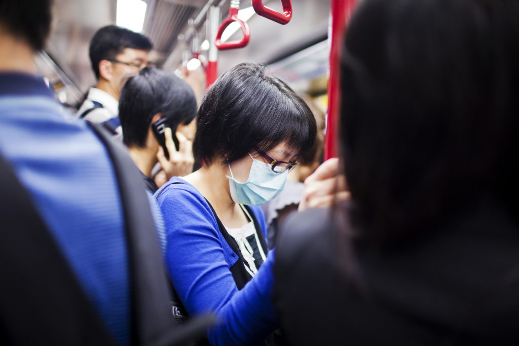 Woman a wearing mask on a crowded subway in Hong Kong