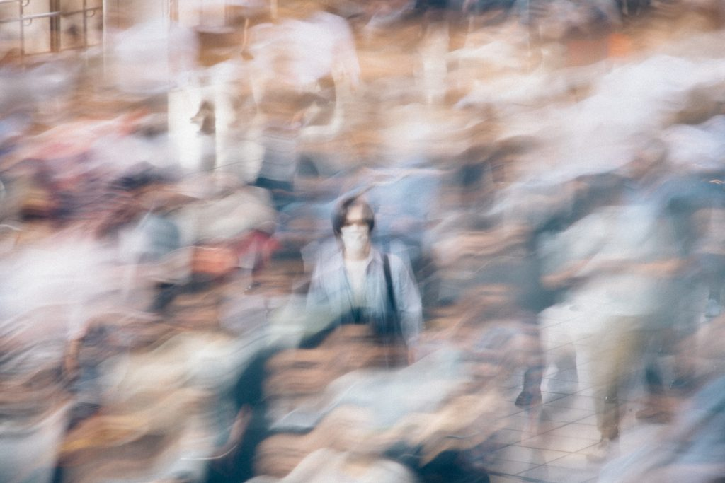 A person wearing a mask stands still at the centre of a crowd as others rush by