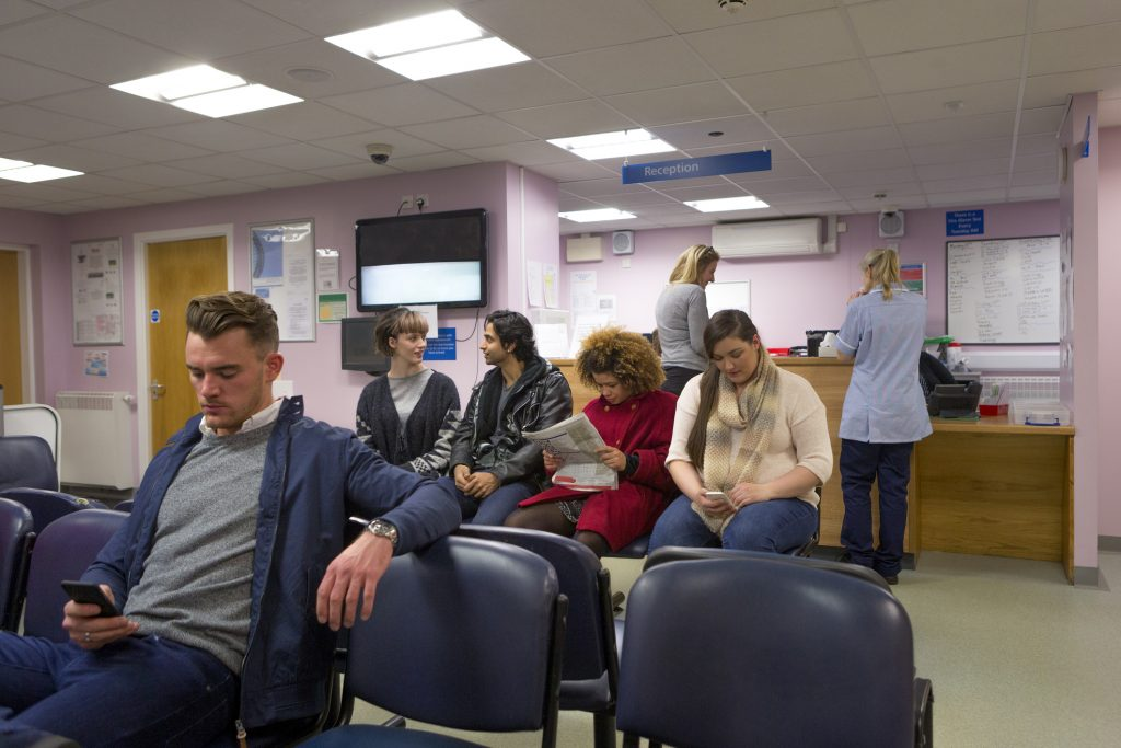 Wide shot of a hospital waiting room with most seats filled with waiting patients