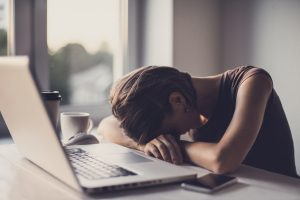 A tired woman rests her head on her desk