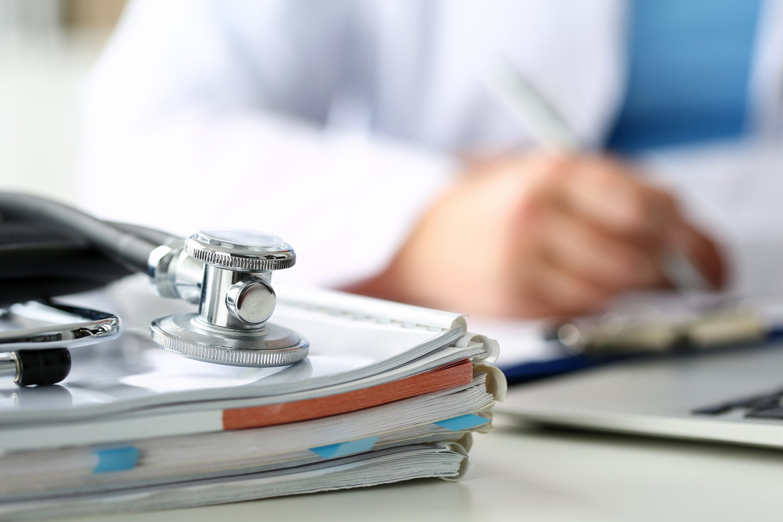 Stethoscope lying on top of medical notes with a doctor writing in the background