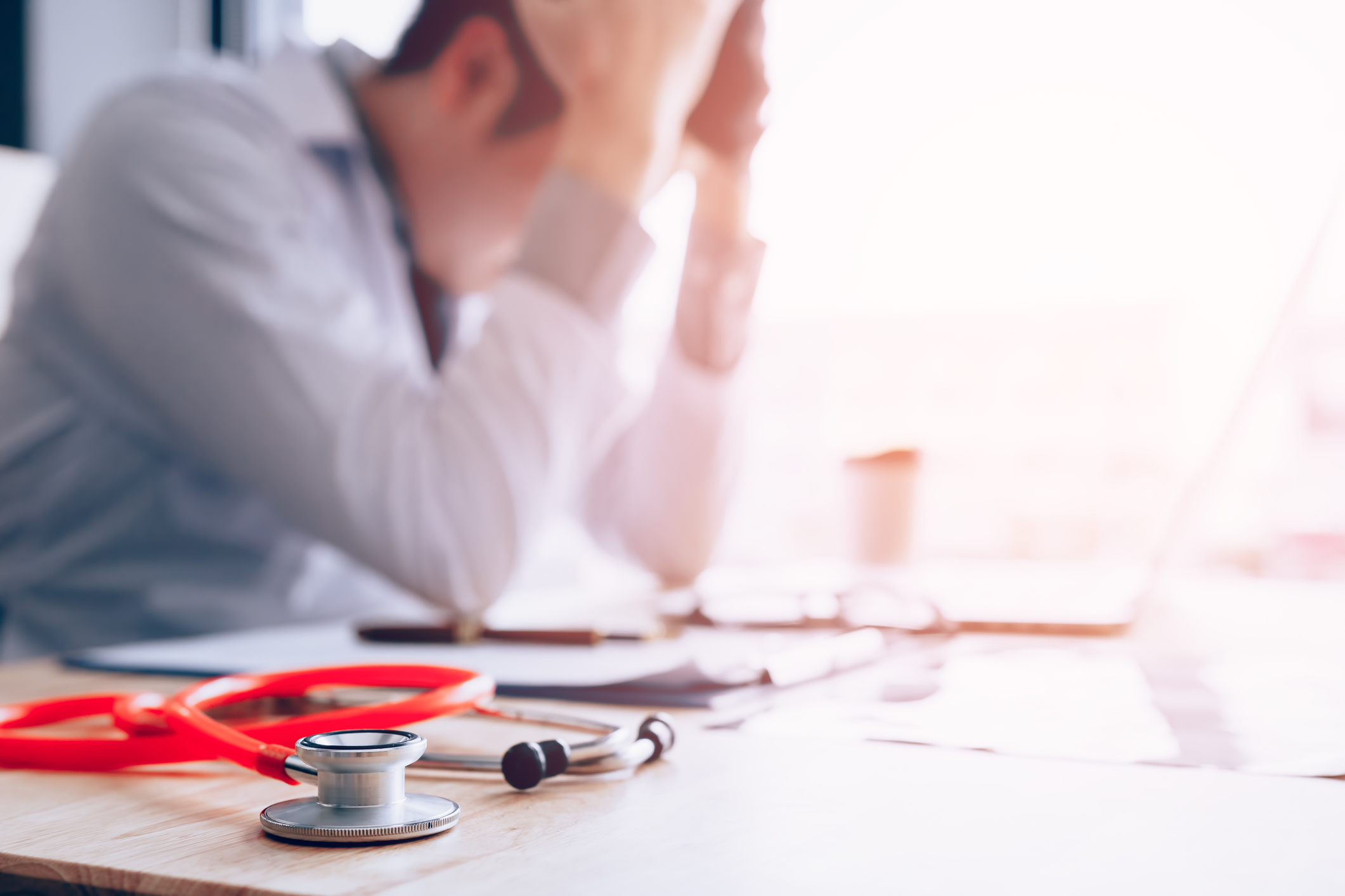 Blurred shot of a tired young male doctor exhausted with his head in his hands