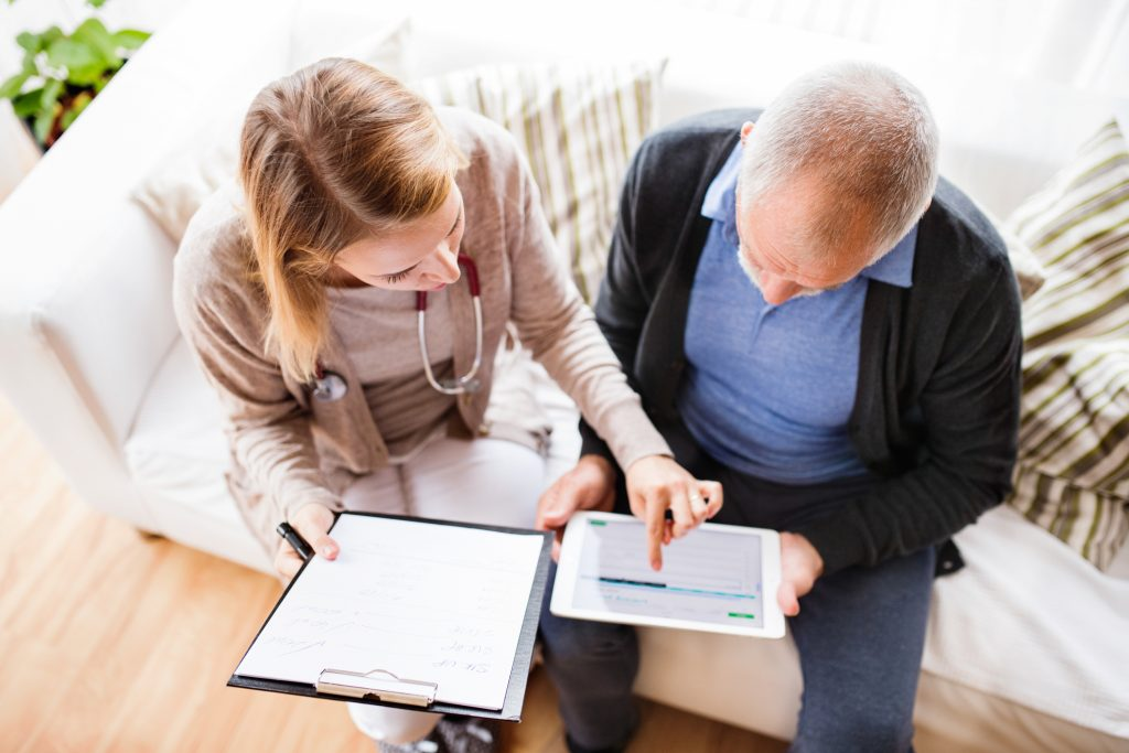 Health worker showing elderly man electronic records during a home visit