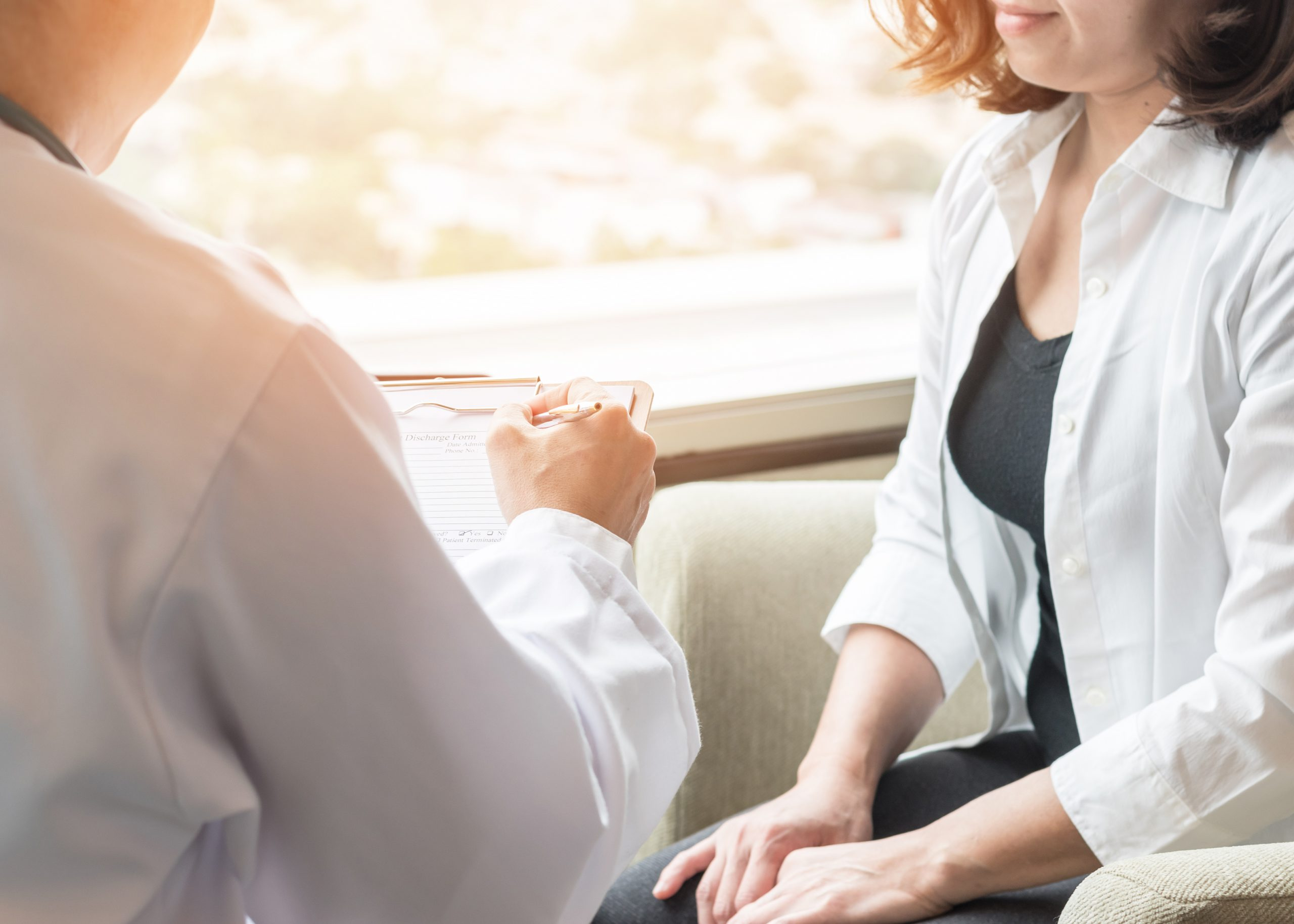 Over the shoulder shot of male physician consulting with a female patient
