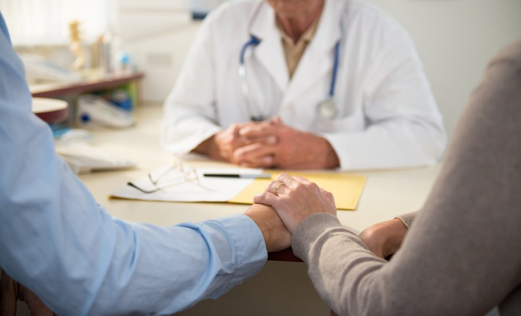Elderly couple holding hands at a desk while consulting a physician