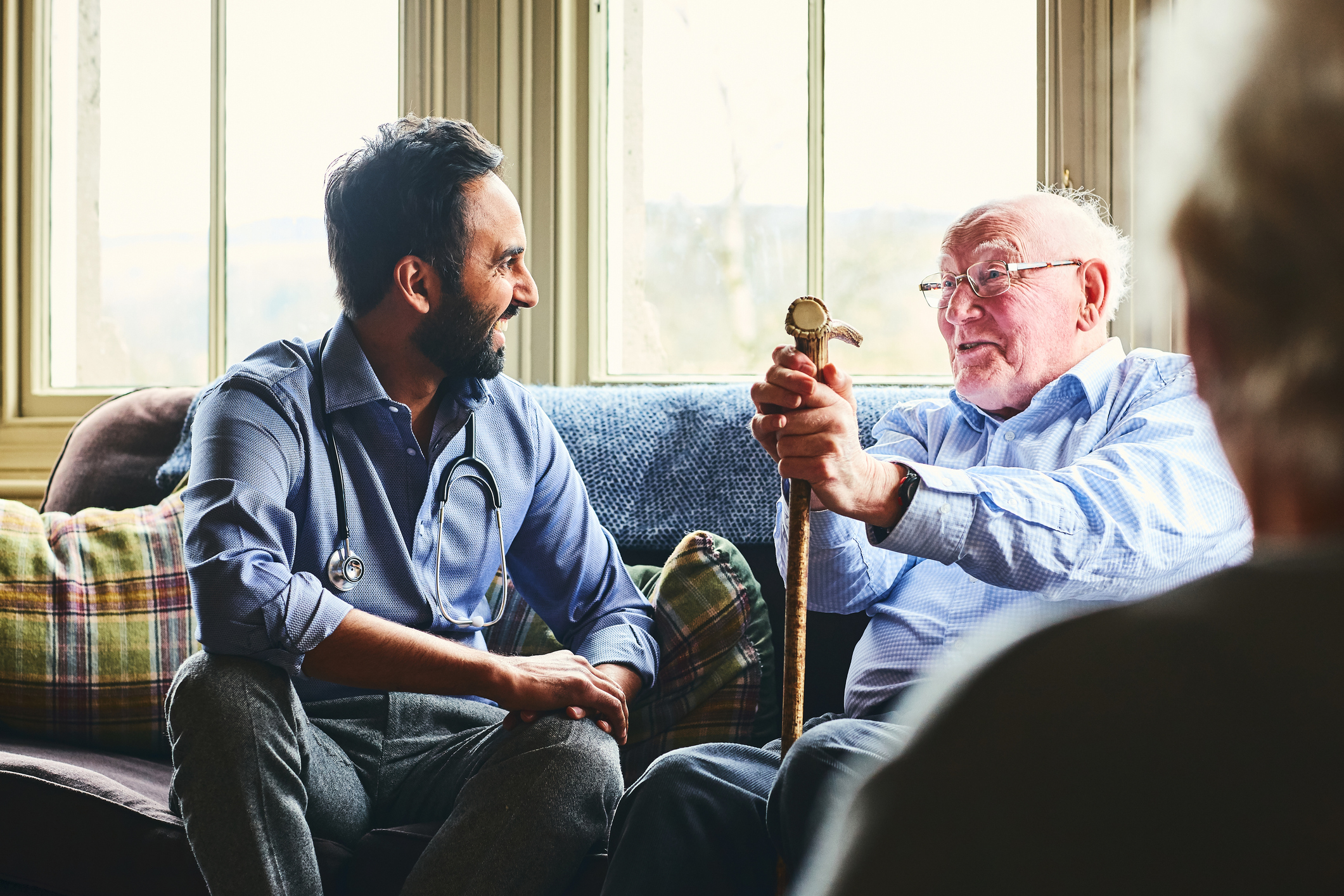 Male physician visiting an elderly man for an at-home visit