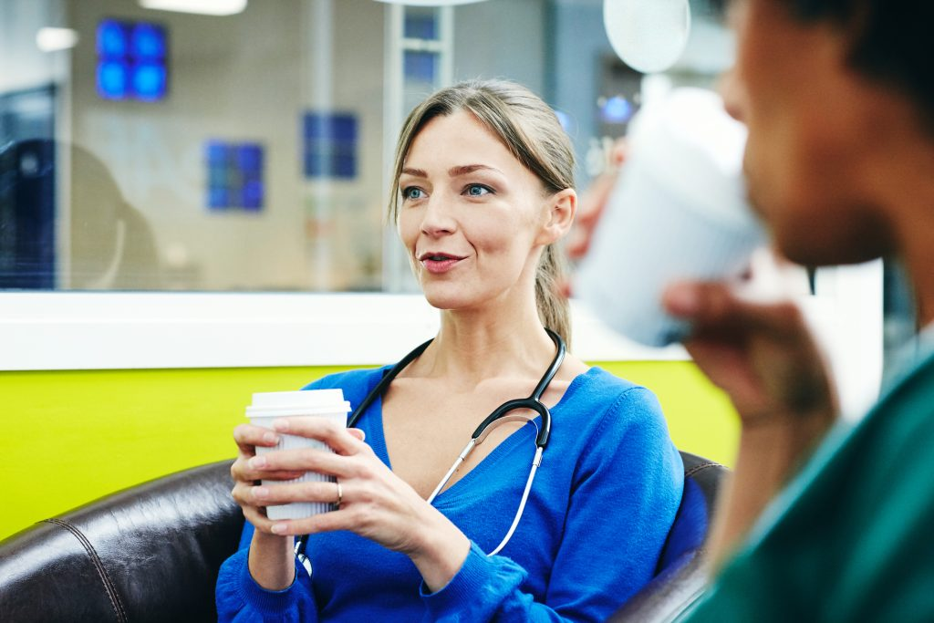 Female Caucasian physician sitting in a doctor's lounge holding a coffee talking to a coworker