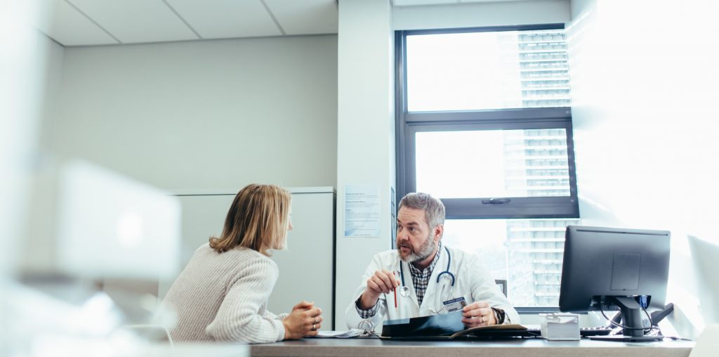 Female patient and male physician sitting at a desk together and talking intensely