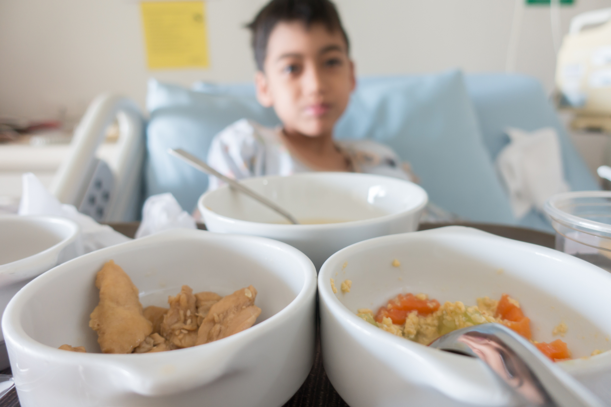 Young boy in hospital bed with tray of food in the foreground