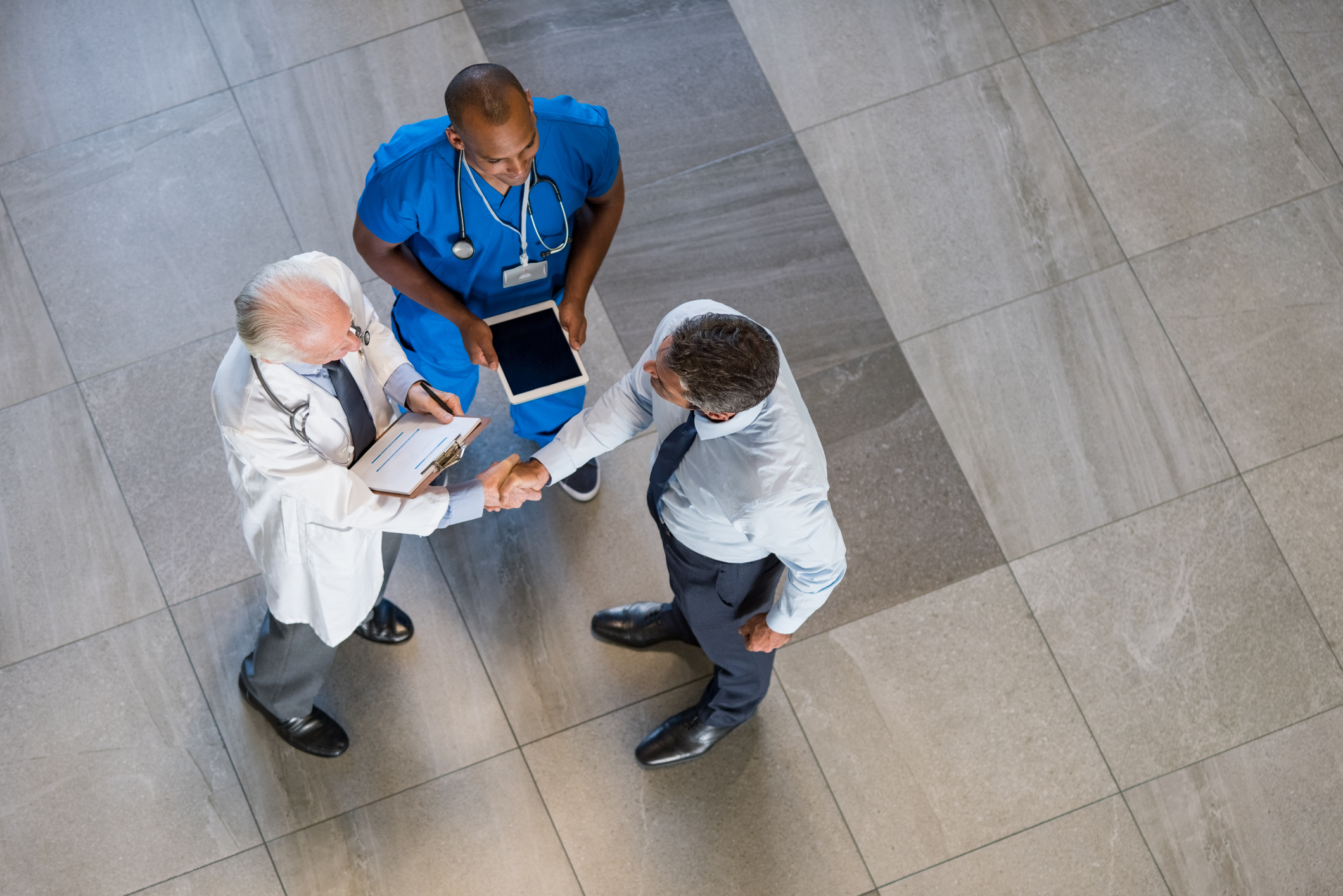 High angle shot of two physicians shaking hands with a pharmacist representative