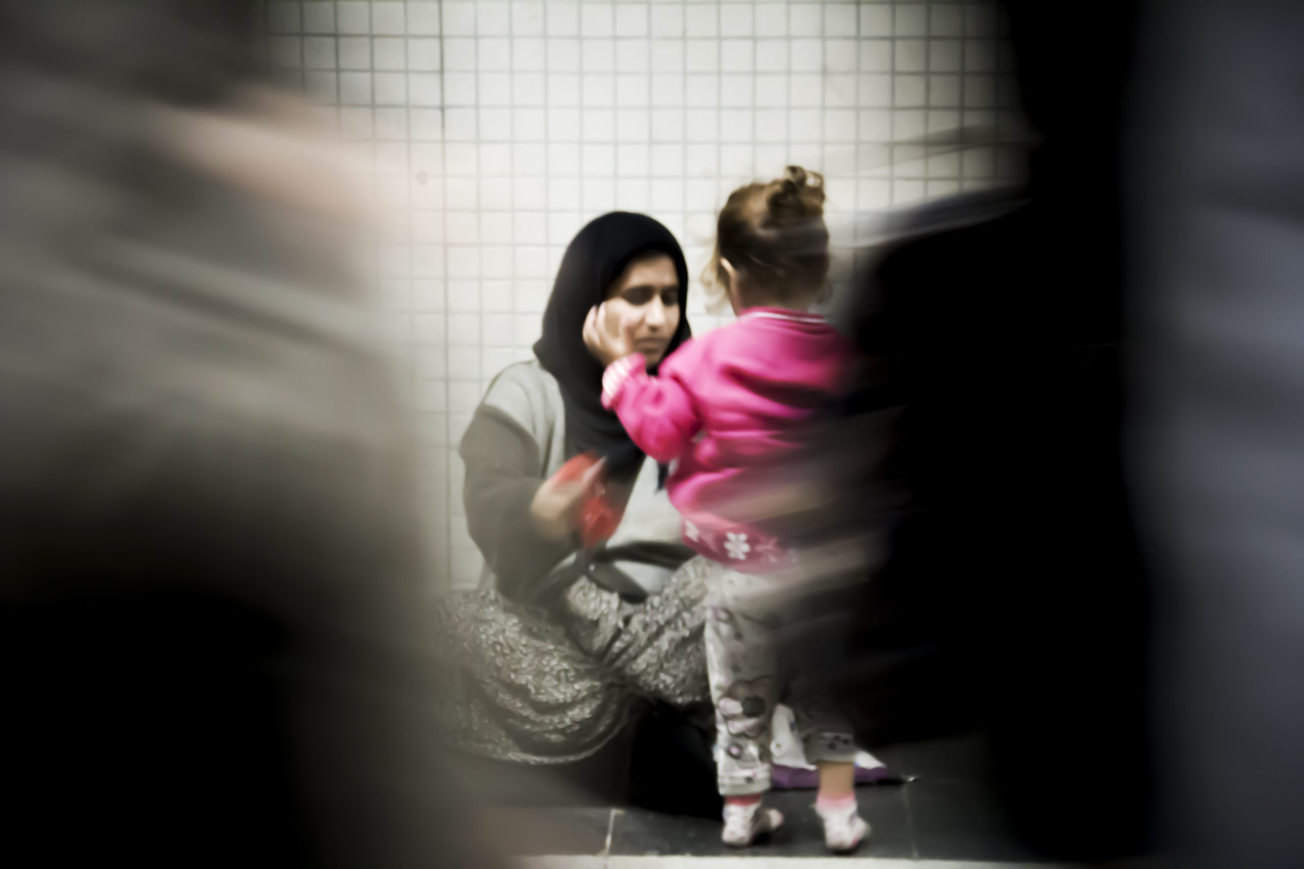 A refugee woman sitting on the floor with her daughter