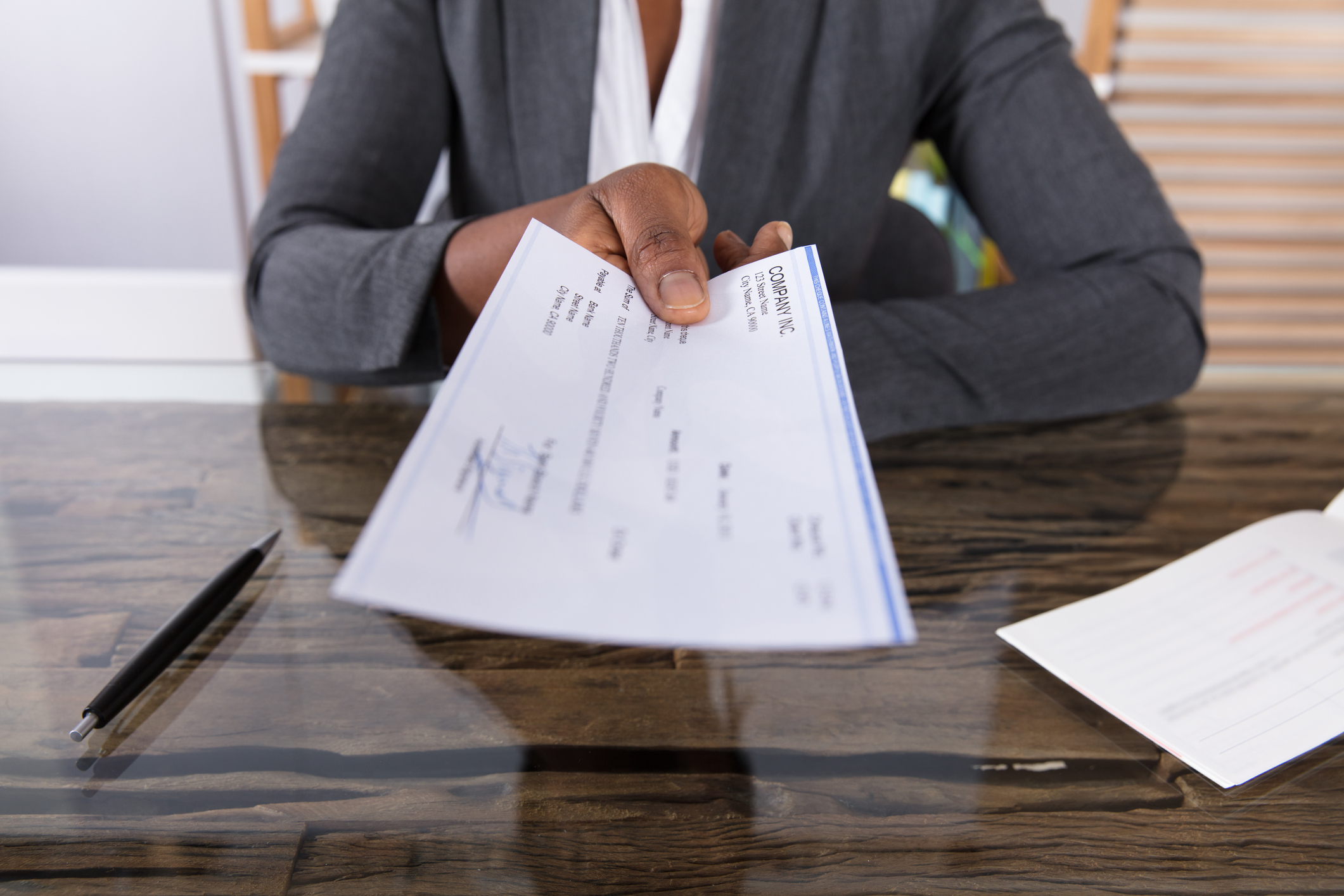 Closeup of a woman in a suit handing a paycheque across a desk
