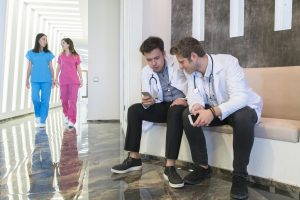 Young doctors sit together looking at their phone screens as other health professionals pass by