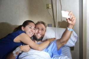 A woman hugs a man lying in a hospital bed as they take a selfie with a smartphone