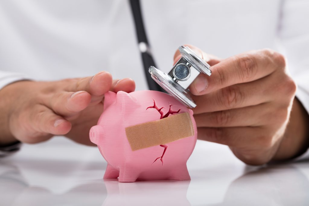 Closeup of a doctor holding a stethoscope up to a broken piggy bank