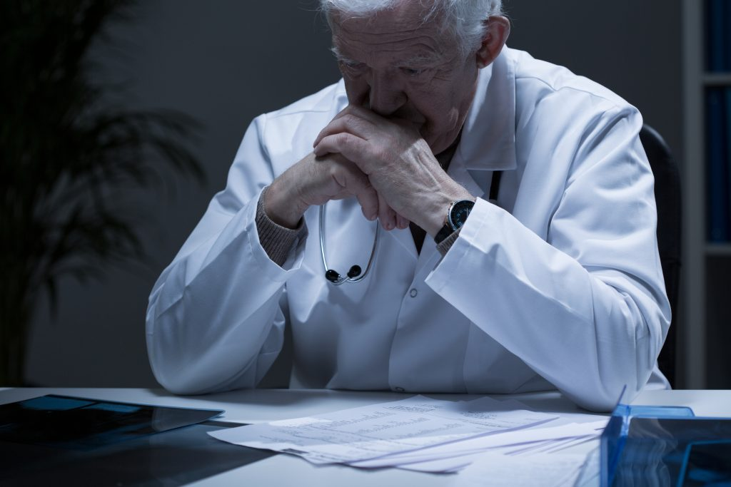 Elderly male physician sitting and looking tired and pensive