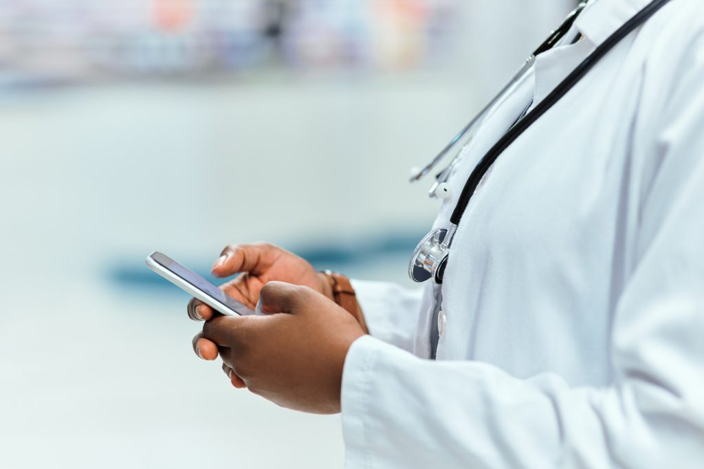 Cropped image of a female physician scrolling on her smartphone