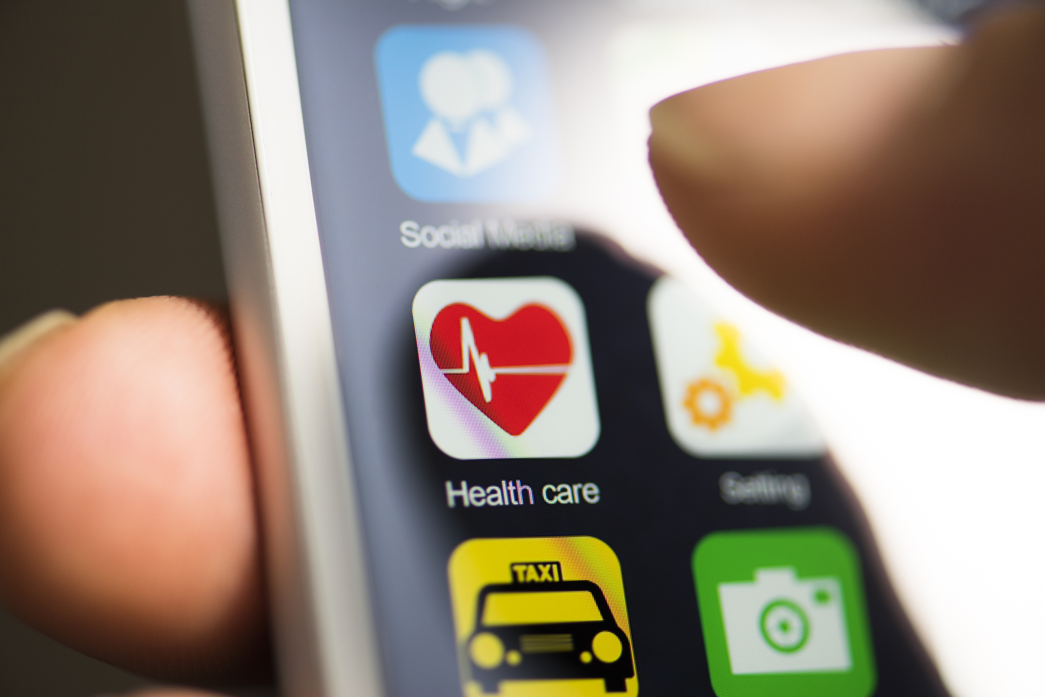 Closeup of smartphone screen with finger hovering over a healthcare app