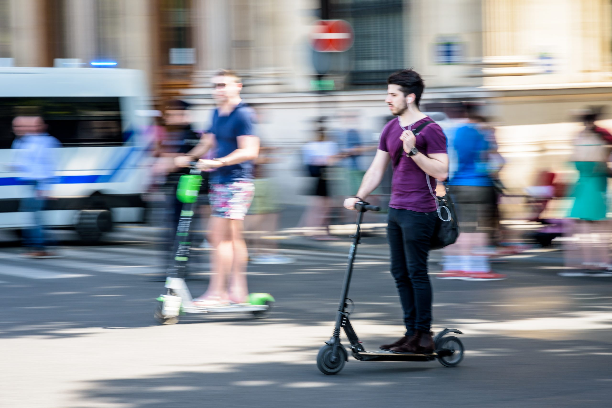 Young man without a helmet riding an electric scooter on a busy city street