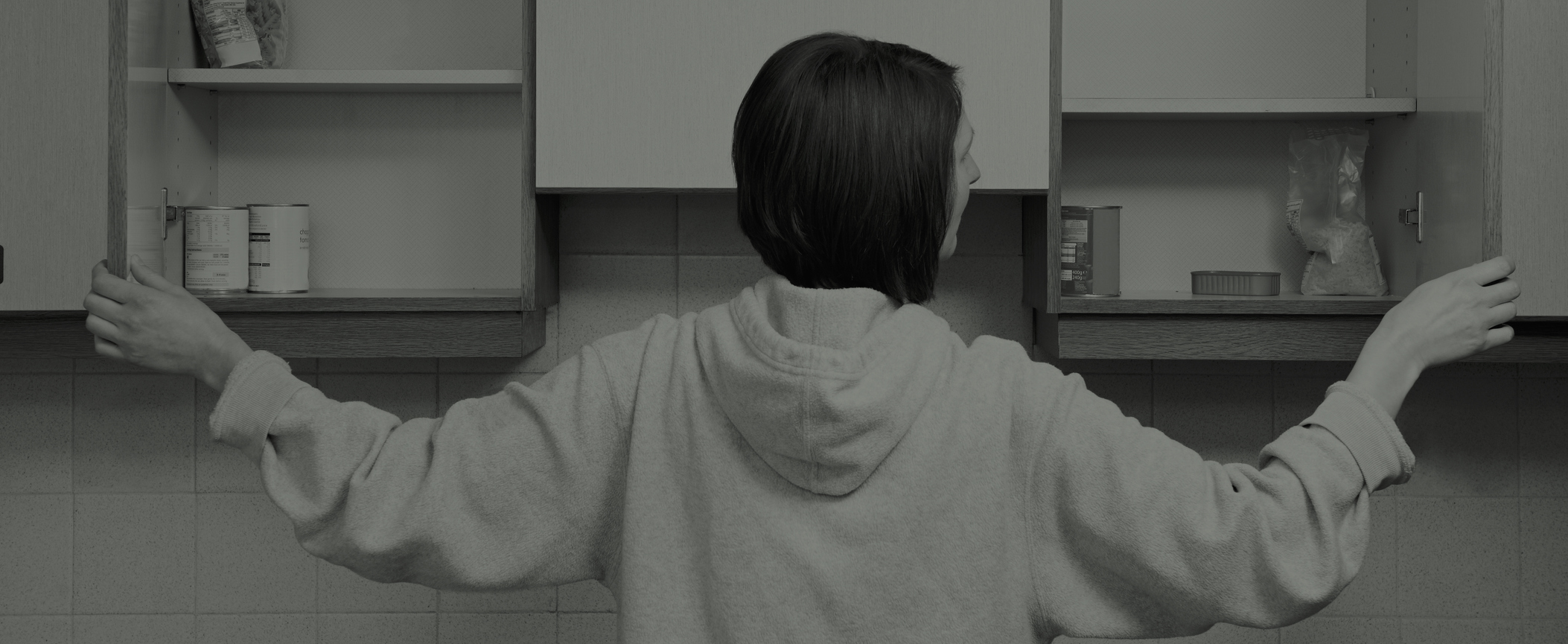 Black and white image of woman opening her empty kitchen cupboards