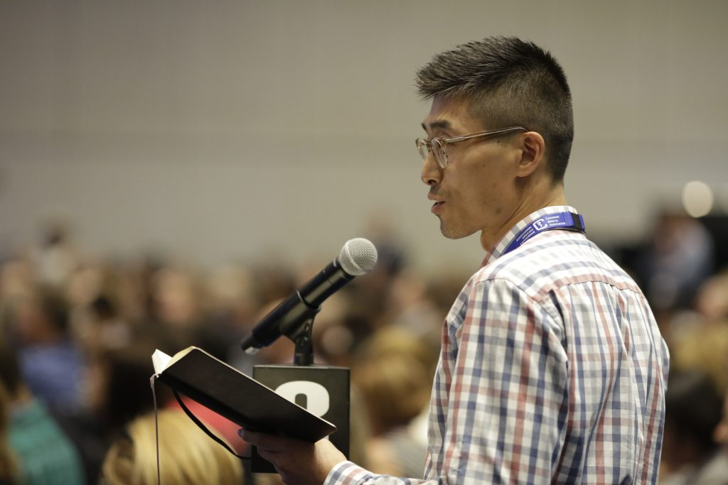 Dr. Edward Xie speaking at the microphone at the Canadian Medical Association annual meeting