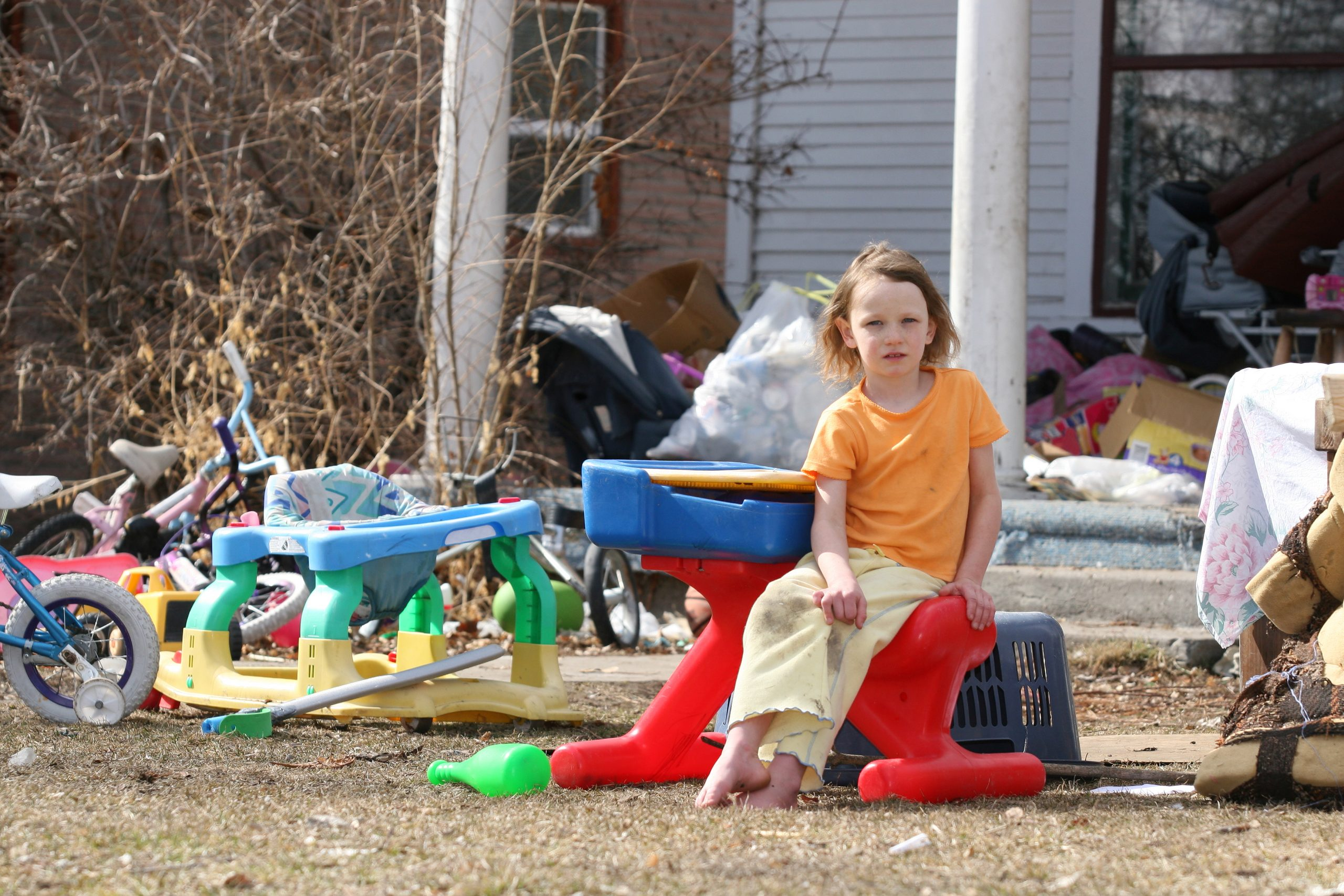 Little girl sits surrounded by junk on the front lawn of a rundown home