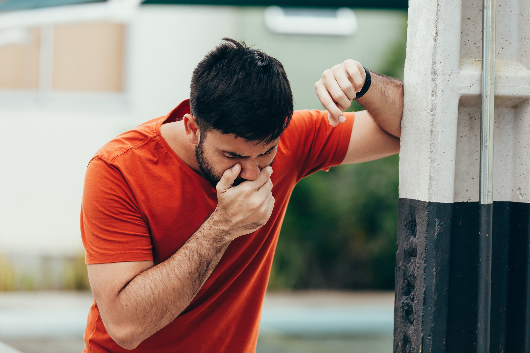 Nauseous man leaning against a wall with a hand to his mouth