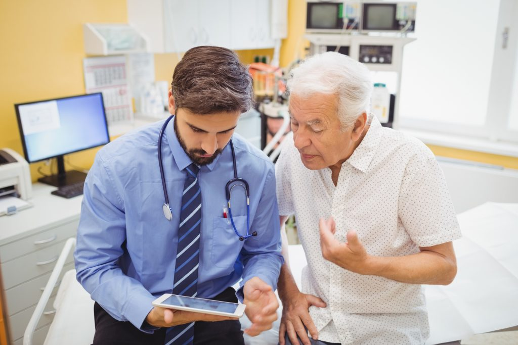 Doctor sitting on a hospital bed with an elderly patient looking at a tablet together