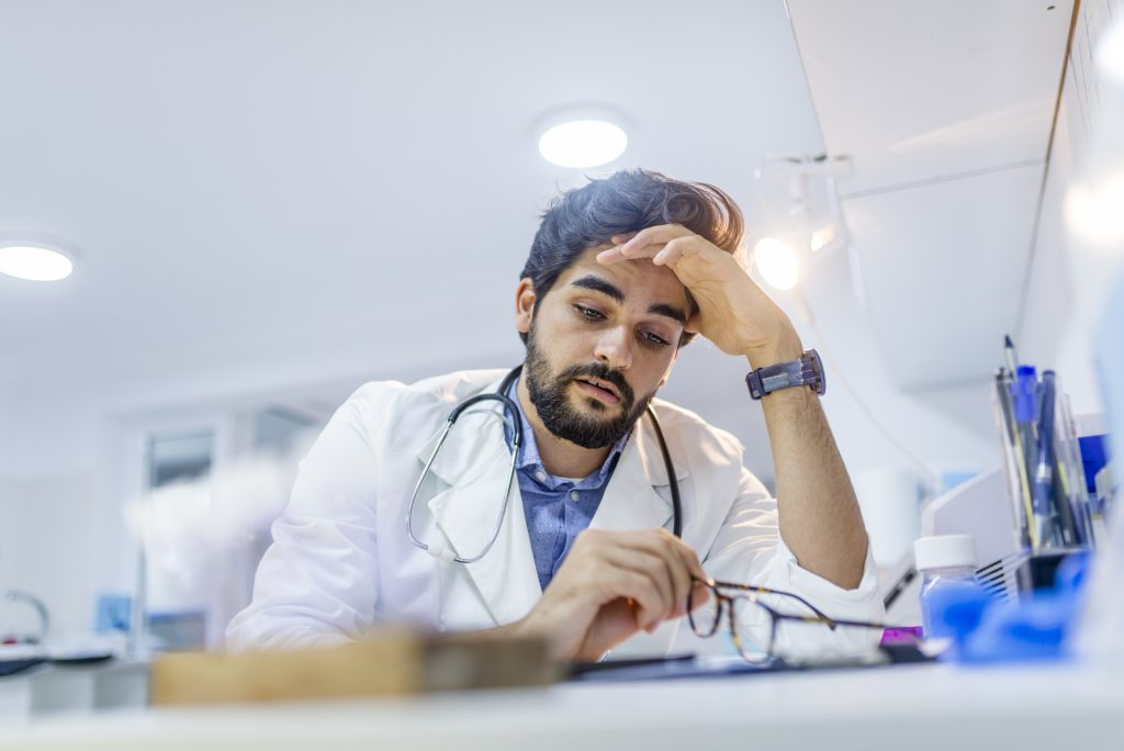 Tired young male doctor looking down at his desk in hospital