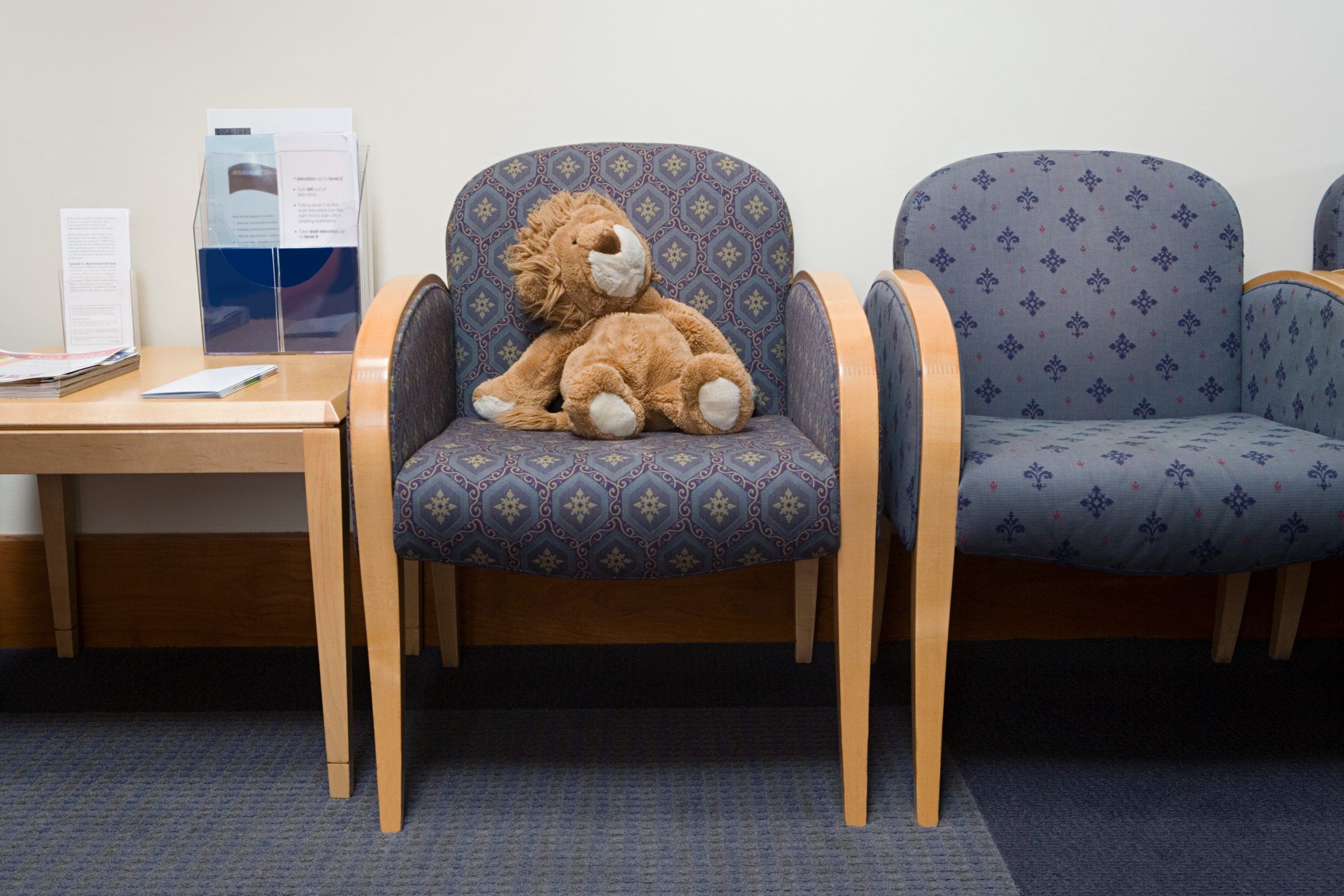 A toy lion forgotten on one of several empty chairs in a clinic waiting room
