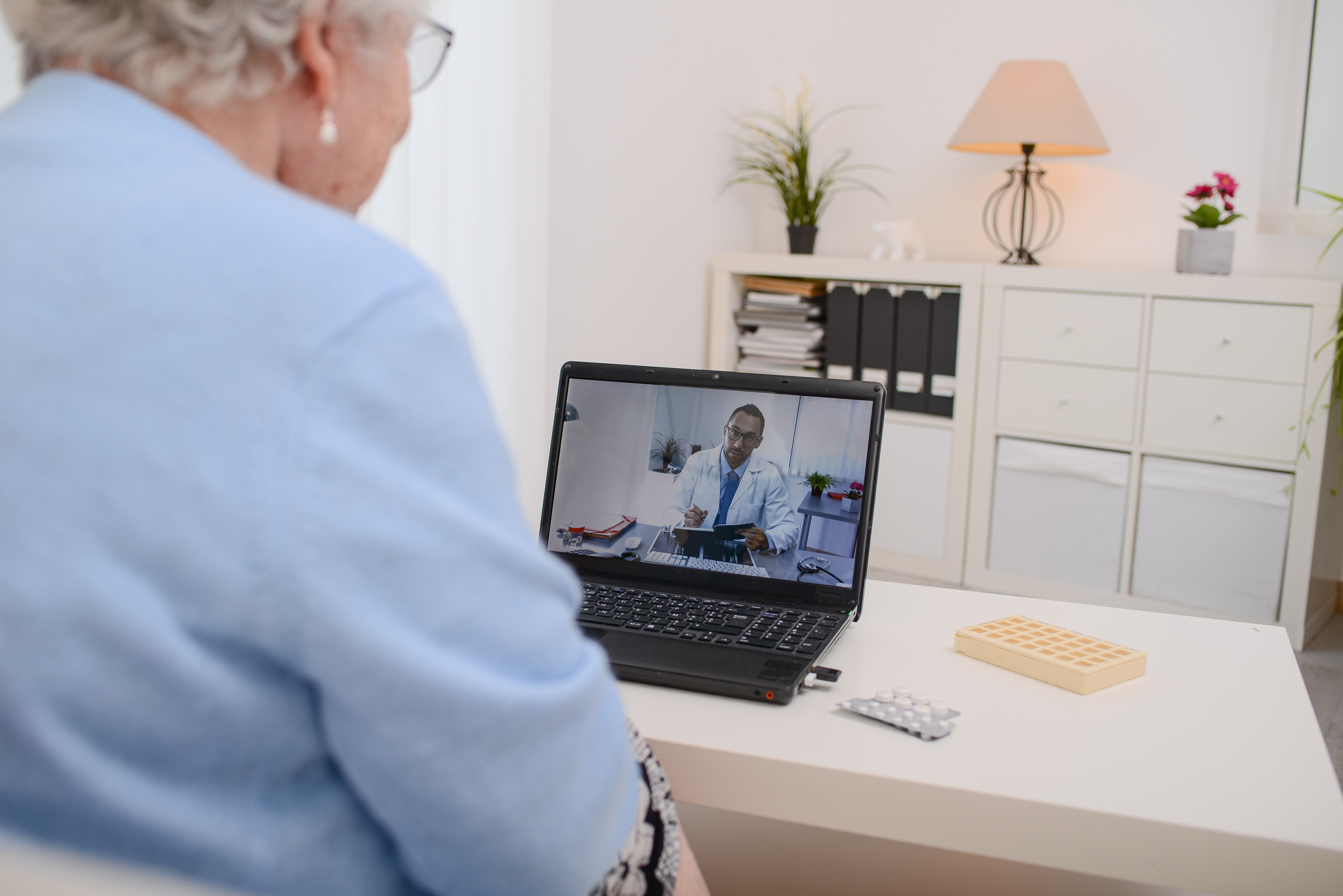 Older woman videochatting with a male physician on her laptop