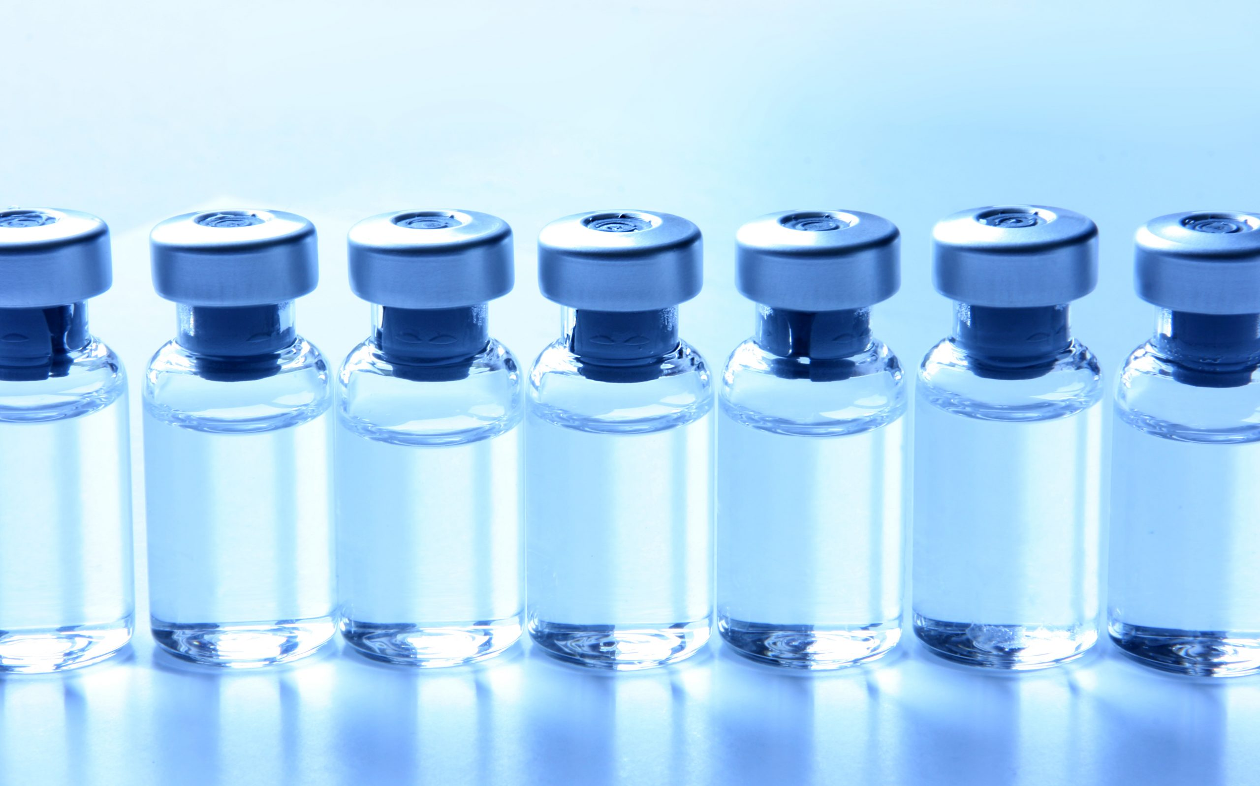 A row of vaccine vials on a light blue background