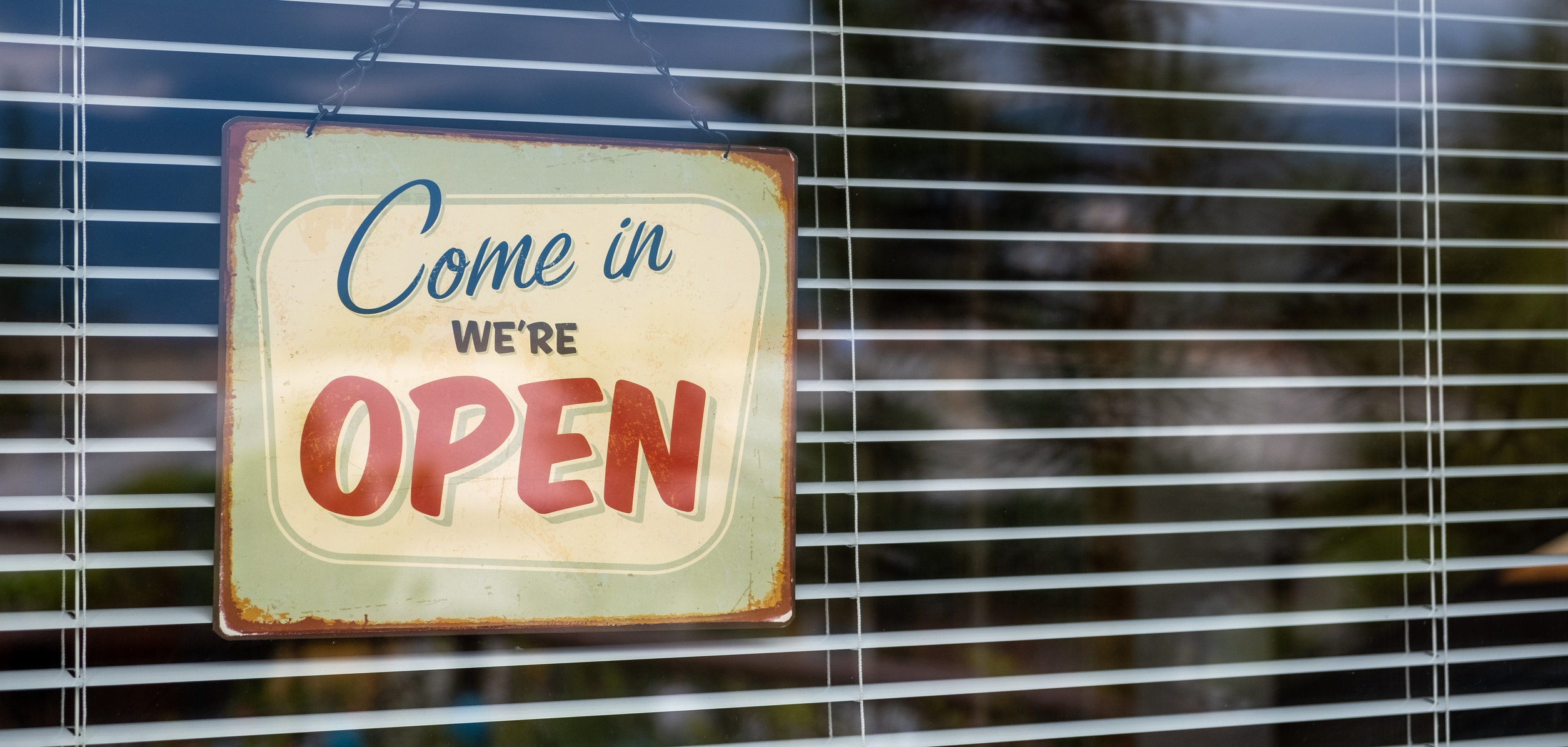"""Store window with a sign saying """"Come in we're open"""""""