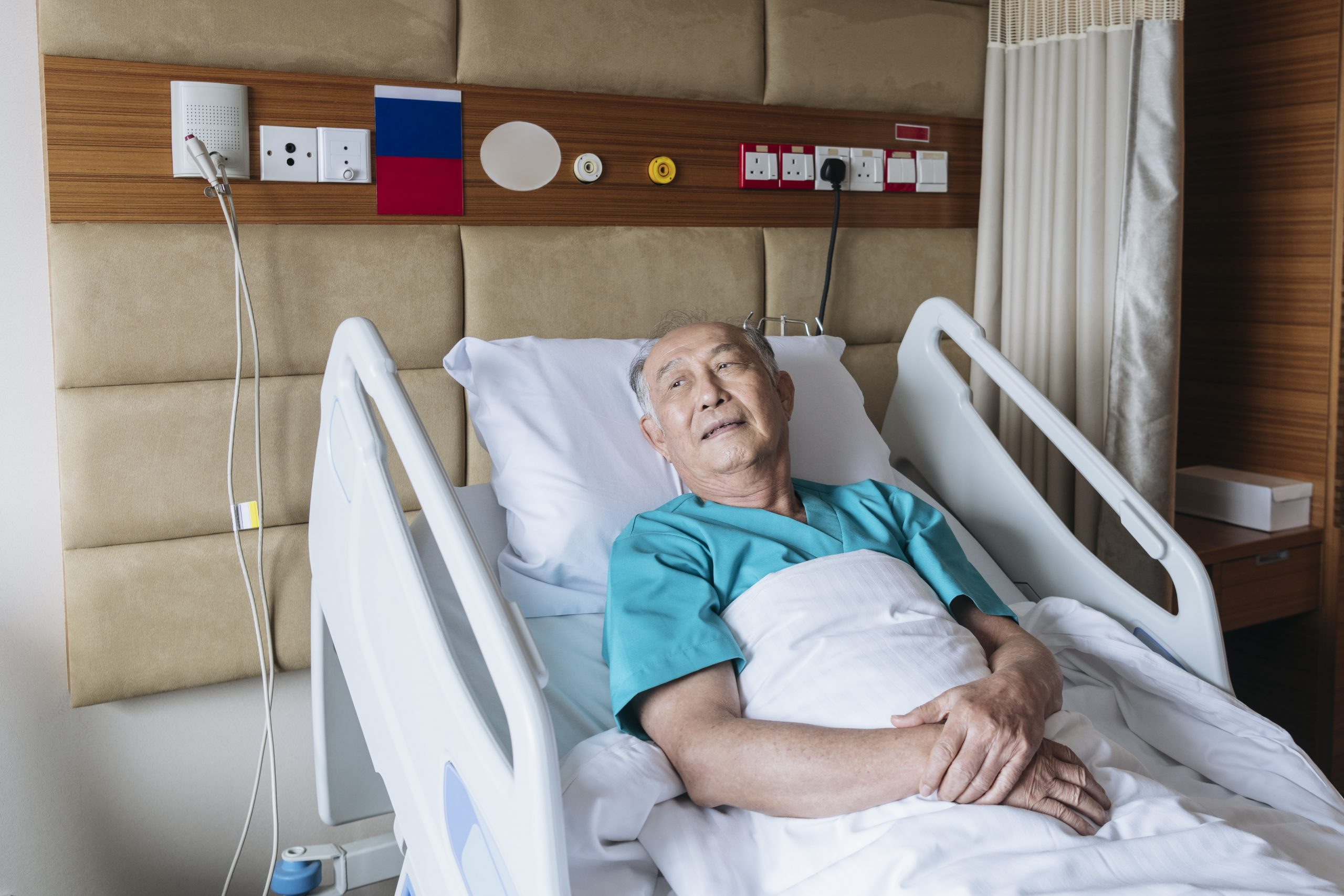 Older Asian man lying in hospital bed looking out the window