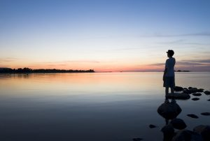 A young boy standing on a rock looks out over a peaceful lake at sunset