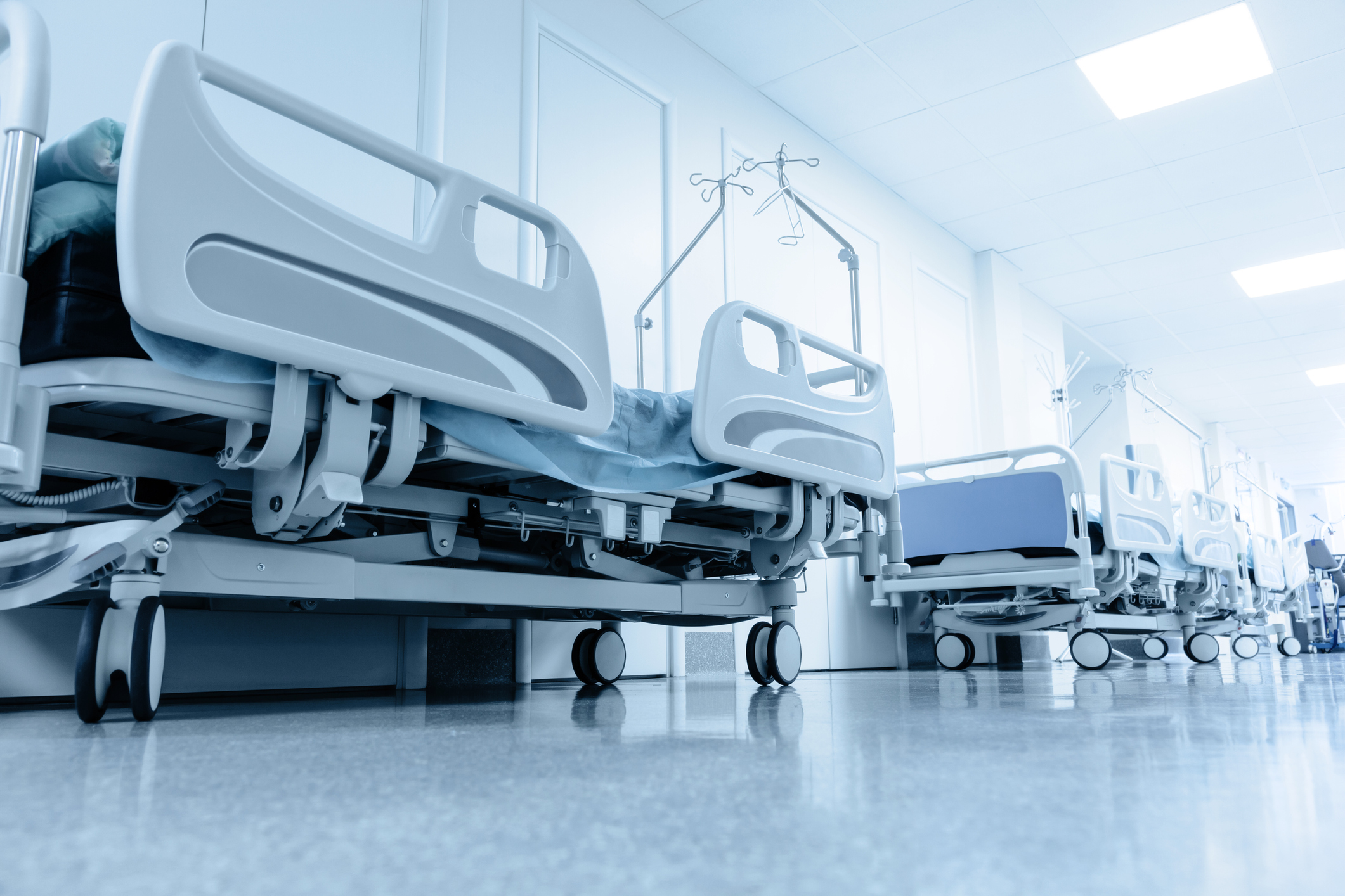 Low angle shot of a hospital hallway lined with empty stretchers