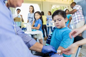 Young boy getting a vaccination with other children and healthcare workers in the background