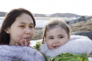 A young Inuit woman and toddler wearing wearing traditional amouti parkas with fur hoods on a tundra