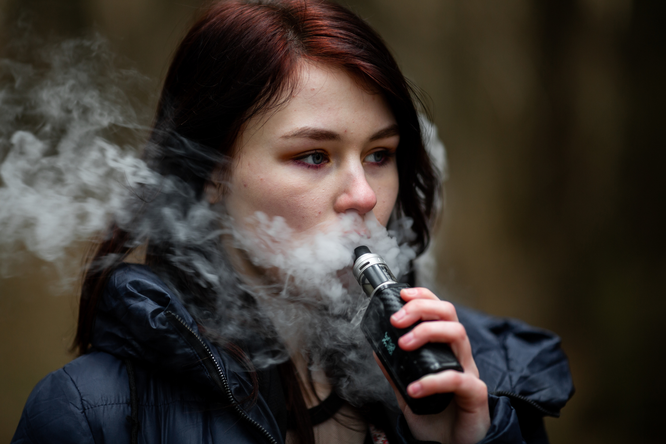 White teenage girl vaping with vapour billowing around her