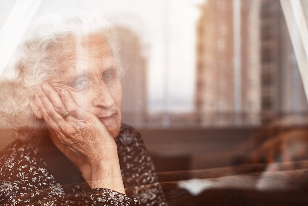 Older woman rests her face on one hand while looking out the window of a retirement home